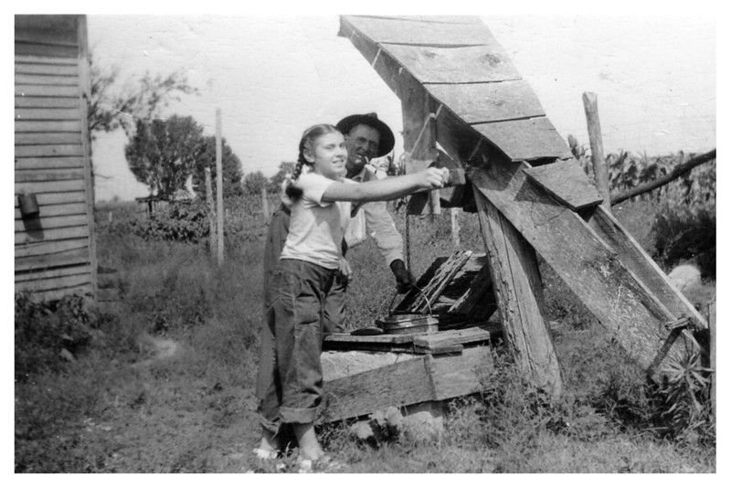 Unknown girl and Clarence Myers at well
