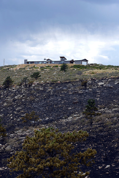 Charred land surrounds a home on Hertha Ridge Thursday, Aug. 18, 2016, after a fire started there Wednesday southeast of Carter Lake. The 73 acre fire was 65 percent contained eary Thursday. (Photo by Jenny Sparks/Loveland Reporter-Herald)