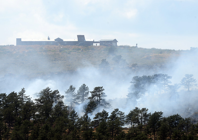 Firefighters protect a home as an 80-acre wildfire burns on Hertha Ridge just southeast of Carter Lake on Wednesday, Aug. 17, 2016. Larimer County Sheriff's Office officials stated the fire was 30 percent contained just before 6 pm.  (Photo by Jenny Sparks/Loveland Reporter-Herald)