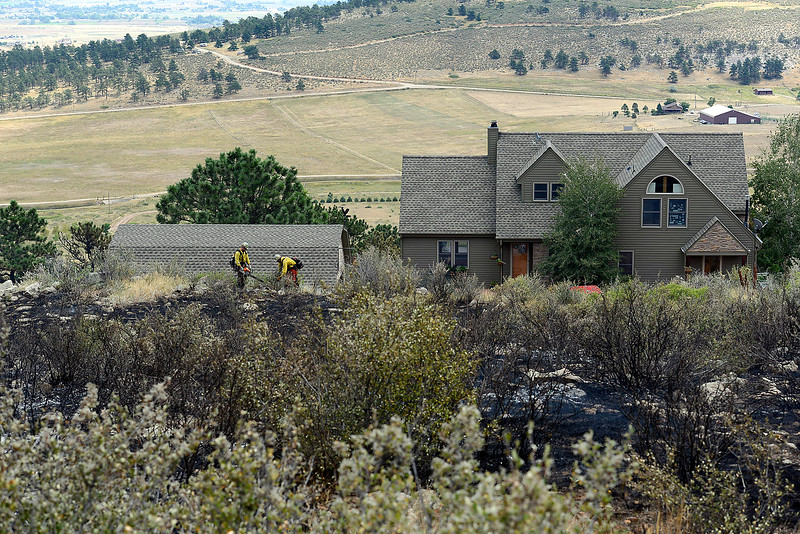 Mike Zimmer, left, and Connor Devore, members of the Larimer Sheriff's Office Wildland crew, remove brush Thursday, Aug. 18, 2016, surrounding a home that firefighters saved during the Hertha Fire southeast of Carter Lake. Teh 73 acre fire was 65 percent contained eary Thursday. (Photo by Jenny Sparks/Loveland Reporter-Herald)