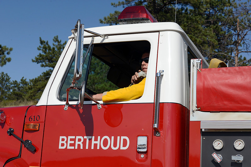 Berthoud Firefighter Jim Thompson talks on his radio as he get a different perspective on an 80-acre wildfire on Hertha Ridge just southeast of Carter Lake on Wednesday, Aug. 17, 2016.  (Photo by Jenny Sparks/Loveland Reporter-Herald)