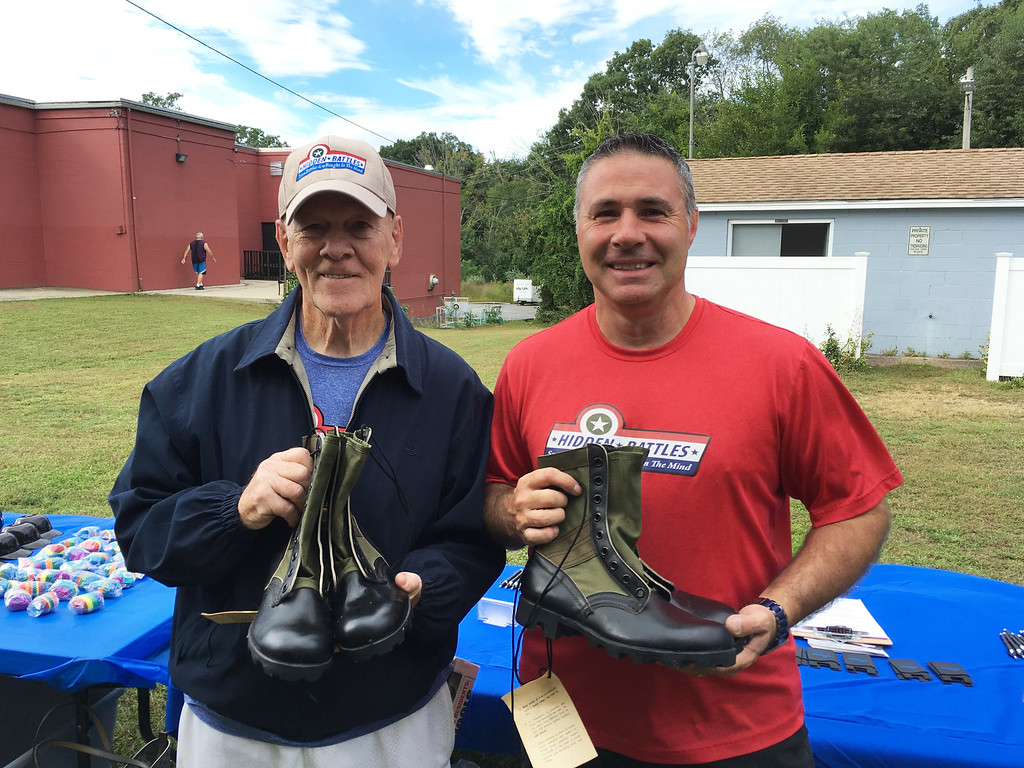 . Retired Army Sgt. 1st Class John P. Cregg and Hidden Battles founder and president Scott J. Hyder, both of Pelham, hold pairs of Vietnam veterans� boots.