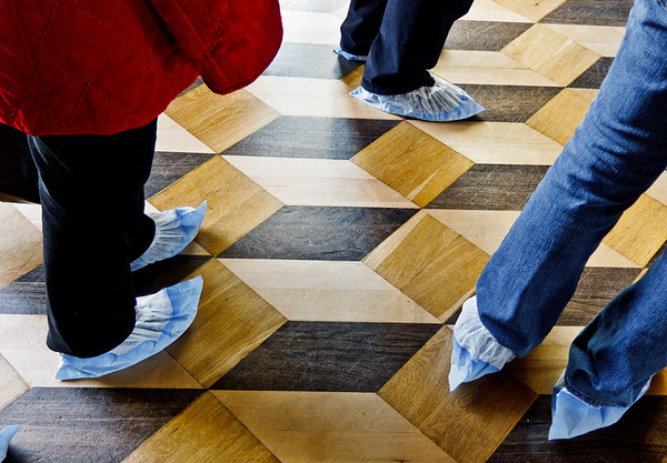 It's a photographic optical illusion, not a mathematical Escher graphic. We wore the plastic thingies over our shoes to protect the floors.