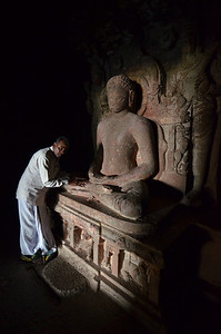Man honoring a statue of a Jina (saint in the Jain religion)