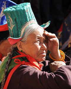 Ladakhi woman watching the Thiksey festival activities.