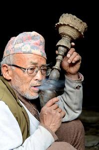 Nepal man smoking an old-style pipe in Bhaktapur, Nepal.