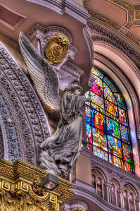 A seraph with the stained glass window of Christ the King and the clerestory in the background. The seraphim have trumpets and adorn the four principle arches of the Church.