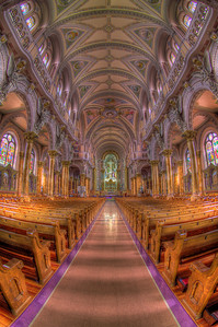 Wide angle shot of the nave, capturing some of the Stations of the Cross and stained glass windows on the side.