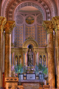 Altar of St. Joseph in the chancel. He is depicted with the staff by which he led the Holy Family into Egypt and back, and each year three times up to the Temple in Jerusalem. Above him is a round fresco of St. Peter's Basilica in Rome, which is a symbol of the Church universal of which St. Joseph is the patron and protector.