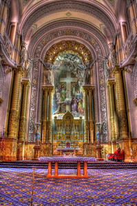 The sanctuary, main and high altar. Notice the six enormous cherubim looking down at the altar from above, with their huge wings, which distinguish them from the angels below the clerestory. The splendor of the Cross of Christ dominates the sanctuary.