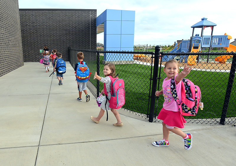 Kindergarteners Keira Deboodt, 5, center, and Brooke Gallegos, 6, right, wave to their parents as they head inside to start their first day of school Friday, Aug. 19, 2016, at the new High Plains School in east Loveland. (Photo by Jenny Sparks/Loveland Reporter-Herald)