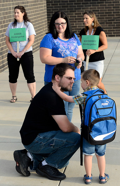 Kindergartener Connor Bashor, 5, says goodbye to his dad, Josh Bashor, as his mom, Christine Bashor, watches before he lines up with his classmates on the first day of school Friday, Aug. 19, 2016, at the new High Plains School in east Loveland. (Photo by Jenny Sparks/Loveland Reporter-Herald)