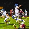 Lunenburg quarterback Colin Murphy hurdles Ayer Shirley's Lucas Sargent. Nashoba Valley Voice/Ed Niser