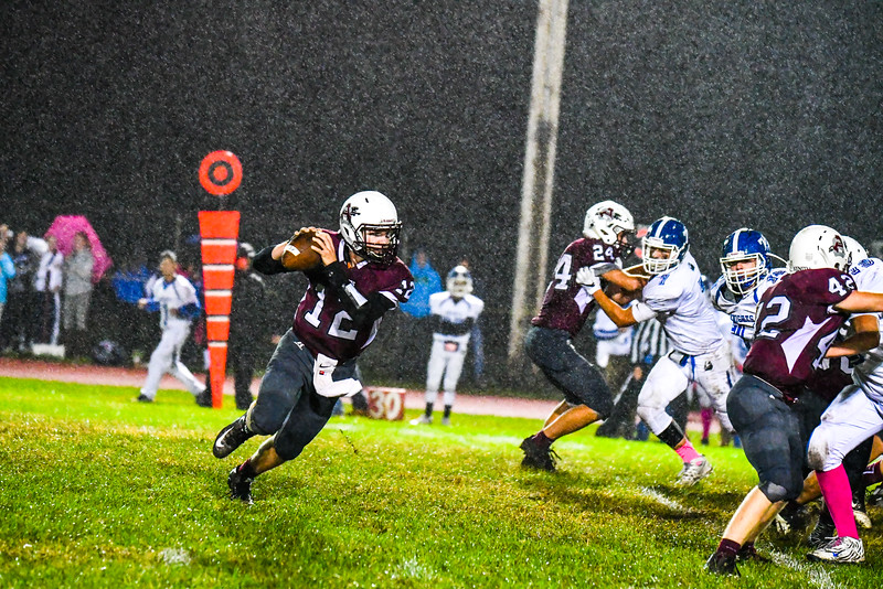 Ayer Shirley quarterback Steven Lawton rolls out of the pocket in the driving rain. Nashoba Valley Voice/Ed Niser