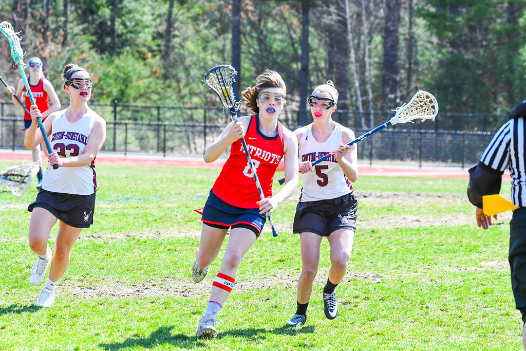 . North Middlesex\'s Molly O\'Neill carries the ball around Groton-Dunstable\'s Abby Fusari. Nashoba Valley Voice/Ed Niser