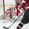 Hudson goaltender Adam Devlin dives for a shot by Groton-Dunstable's Liam McDonough (5). Nashoba Valley Voice/Ed Niser