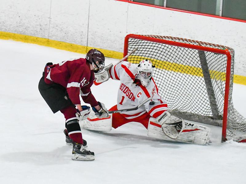 Groton-Dunstable's Andrew Berube has his shot deflect off the arm of Hudson goaltender Adam Devlin. Nashoba Valley Voice/Ed Niser