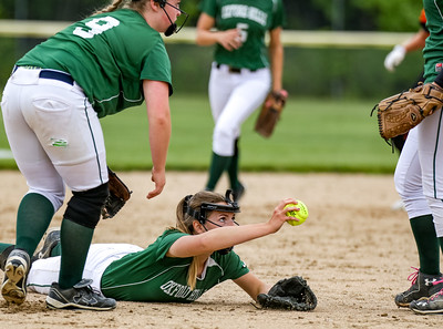 Oxford Hills' Kaisa Heikkinen reaches up to half the ball to teammate Cody Akers after catching a fly ball to end the second inning.