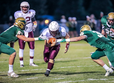 Edward Little's Caden Begos prepares to slip by Oxford Hills' Connor Bickford and Jordan Silver in the first half of last night's game at the Gouin Field in South Paris.