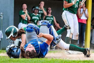 Lawrence catcher Haley Holt and Oxford Hills pinch runner Brooke Carson tangle up after Carson scored on an errant throw to first base.