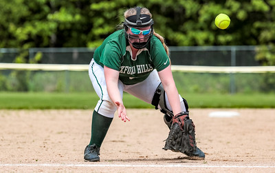 Oxford Hills' third baseman Kenzie Kahkonen attempts to recover after misplaying a ground ball.