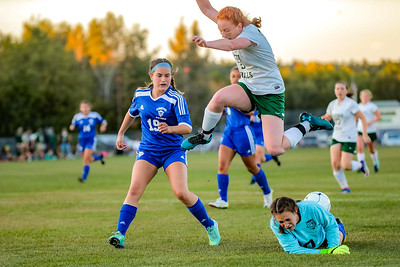 Oxord Hills' Julia Colby goes airborne to avoid Lewiston goalie Gemma Landry after Landry came out for the slide tackle.