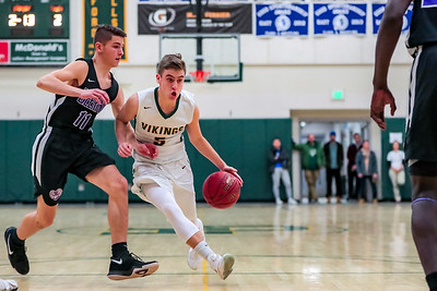 Oxford Hills' Spencer Strong dives the lane defended by Deering's Max Morrione in the first half of play last night in South Paris.