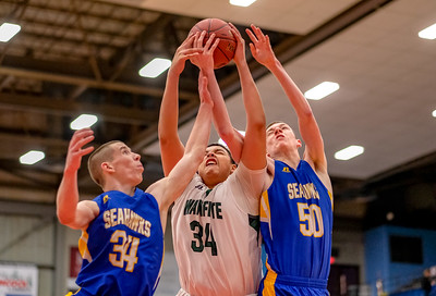 Boothbay's Hunter Crocker and teammate Nick Simpson (right) battle for a rebound with Waynflete's Dominick Campbell.