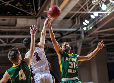 Oxford Hills' Atreyu Keniston (right) and Spencer Strong battle for a rebound against Edward Little's Tyler Morin  in the first half of their game at the Cross Insurance Arena in Portland yesterday.