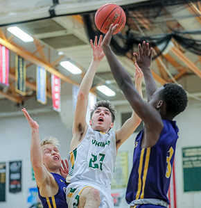 Oxford Hillls' Colby Huckins puts up a floater for two points guarded by Cheverus' Luke Knowles (left) and Bryant Nsengiyumva.
