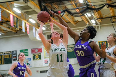 After an offensive rebound, Oxford Hills Maggie Hartnett goes up for a shot as Deering's Gloria Muka tries to get a hand on the ball.