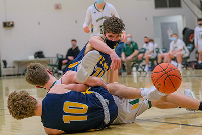 Mt. Blue's Jayden Meader reaches for a loose ball while tangled with Oxford Hills' Teigan Pelletier and teammate Hayden Dippner.