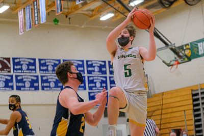 Oxford Hills' Eli Soehren goes to the basket guarded by Mt. Blue's Seth Pinkham.