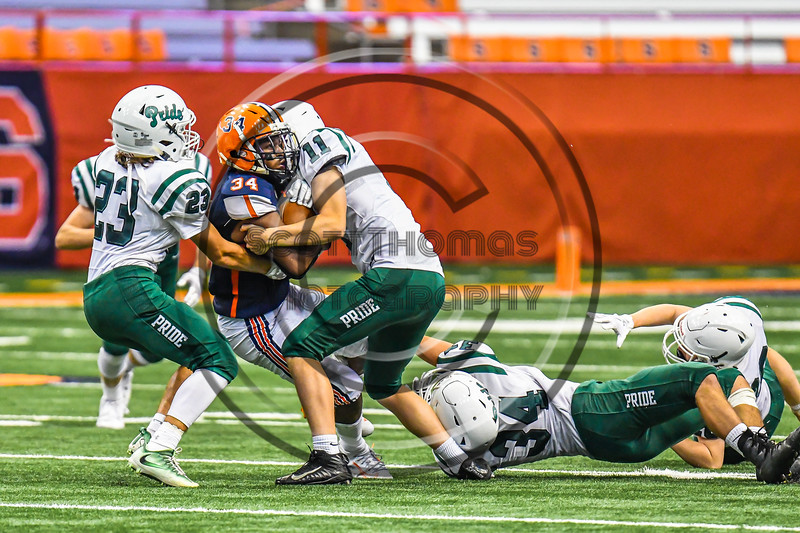 Liverpool Warriors Dakari Mack (34) running with the ball gets tackled by Fayetteville-Manlius Hornets defenders Alexander Dauksza (11), Jack VanValkenburth (23) and Jacob Porzucek (34) in the 2019 Kickoff Classic at the Carrier Dome in Syracuse, New York. Liverpool won 21-7.