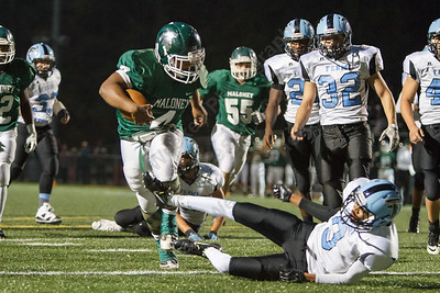 Maloney's Handy Ellison (4) runs through Fermi's Tyshawn Cunningham (9) Friday at Falcon Field in Meriden September,19 2014 | Justin Weekes / For the Record-Journal