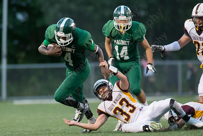 Maloney's Jaron Cogwell (4) breaks a tackle attempt from South Windsor's Jarod Sullivan (33) Friday at Falcon Field in Meriden Sep. 11, 2015 | Justin Weekes / For the Record-Journal