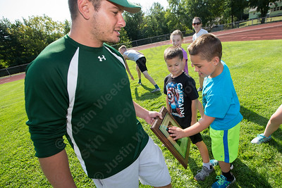 Will Cumbeilibye 8 of Plantsville touches the Rob Szymaszek memorial plaque held  by Maloney's head football coach Kevin Frederick before running the Greenbay a running drill from the Greenbay Packers Sunday at Maloney high School in Meriden Sep. 4, 2016 | Justin Weekes / For the Record-Journal