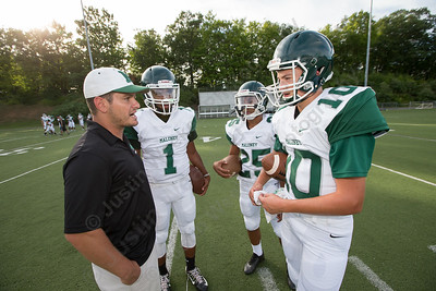Maloney's head coach Kevin Frederick talks with the quarterback core Friday during a pre season scrimmage with Berlin at Sage Park in Berlin Sep. 2, 2016 | Justin Weekes / For the Record-Journal