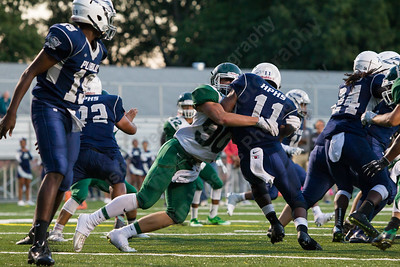 Maloney's Kyle Carlson (90) gets penetration brings down Hartford's Lavarey Banton (11) for a loss  Friday at Falcon Field in Meriden Sep. 16, 2016 | Justin Weekes / For the Record-Journal