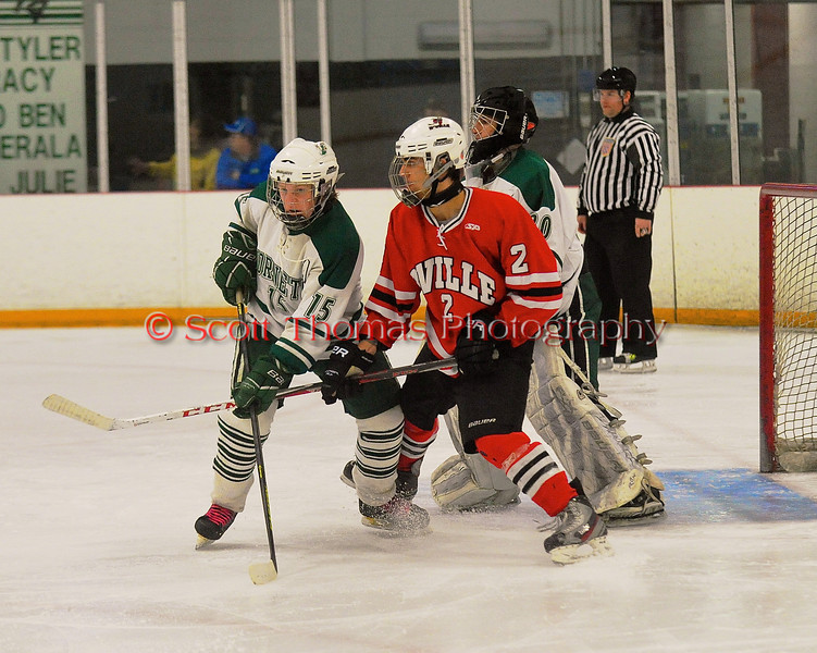 Baldwinsville Bees Luke McCaffrey (2) battles for position with Fayetteville-Manlius Hornets defensemen Tyler Tracy (15) at Cicero Twin Rinks in Cicero, New York on Friday, February 7, 2014.  Baldwinsville won 2-1 in Overtime. © Scott Thomas Photography
