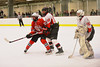 Baldwinsville Bees Tyler Weber (28) battles for position in front of the net with Fulton Red Raiders defensemen Nick Meyer (12) and goaltender Spencer Evans (35) at the Fulton Community Ice Arena in Fulton, New York on Friday, January 10, 2014.  Baldwinsville won 4-1.