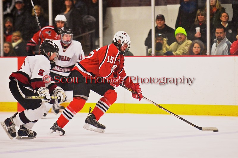 Baldwinsville Bees Charlie Bertrand (15) with the puck against the Syracuse Cougars at Meachem Ice Rink in Syracuse, New York on Friday, January 16, 2015.  Syracuse won 3-1.
