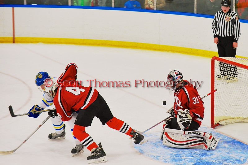 Baldwinsville Bees goalie Matt Sabourin (31) makes a save while Ben Dwyer (4) checks a West Genesee Wildcats player at Shove Park in Camillus, New York on Friday, January 9, 2015. Game ended in a 3-3 tie.