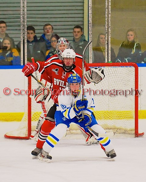 West Genesee Wildcats Carson Hayes (16) sets up inf front of Baldwinsville Bees defenders Charlie Bertrand (15) and goalie Matt Sabourin (31) at Shove Park in Camillus, New York on Friday, January 9, 2015. Game ended in a 3-3 tie.