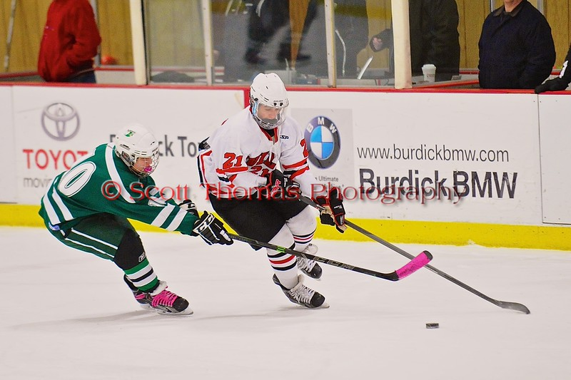 Baldwinsville Bees Adam Tretowicz (21) skates with the puck past Fayetteville-Manlius Hornets Mikkal Toia (10) at the Greater Baldwinsville Ice Arena in Baldwinsville, New York on Tuesday January 6, 2015.  Baldwinsville won 6-1.