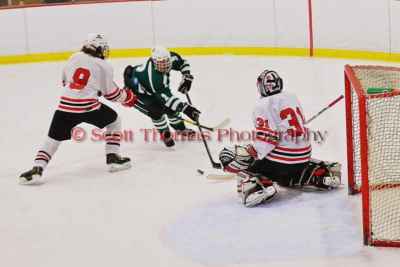 Fayetteville-Manlius Hornets Garrett Zogby (2) being defended by Baldwinsville Bees Jacob Norton (9) and goalie Matt Sabourin (31) at the Greater Baldwinsville Ice Arena in Baldwinsville, New York on Tuesday January 6, 2015.  Baldwinsville won 6-1.