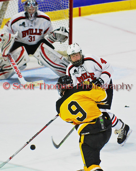 Baldwinsville Bees Ben Dwyer (4) defending against McQuaid Black Knights Ryan Talty (9) in NYSPHSAA Division I Boys Hockey Championships at the Utica Memorial Auditorium in Utica, New York on Sunday, March 15, 2015.  McQuaid won 6-2.