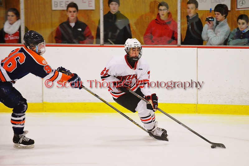 Baldwinsville Bees Adam Tretowicz (21) carries the puck past Liverpool Warriors defender Kyle Terzini (96) at the Greater Baldwinsville Ice Arena in Baldwinsville, New York on Tuesday December 2, 2014.  Baldwinsville won 4-0.