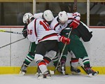 Baldwinsville Bees Carson Hayes (16) and David Eckmann (19) tie up a couple of Fayetteville-Manlius Hornets players along the boards at the Lysander Ice Arena in a Section III Division I Boy ...