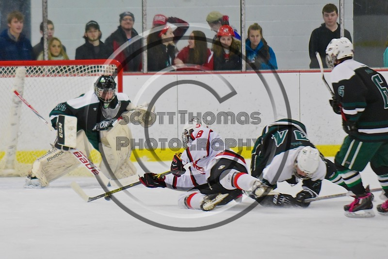 Baldwinsville Bees Garrett Gray (18) gets taken down by Fayetteville-Manlius Hornets Tommy Guilfoil (24) at the Lysander Ice Arena in a Section III Division I Boys Hockey Playoff game at Baldwinsville, New York on Thursday February 18, 2016.  Baldwinsville won 5-0.